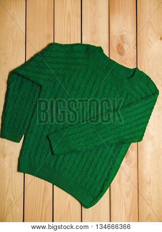 Green knitted sweater on a wooden background. top view