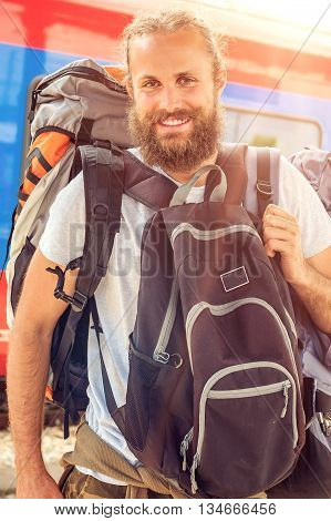 Closeup of handsome tourist traveler standing with huge luggage at the railway station near the tracks