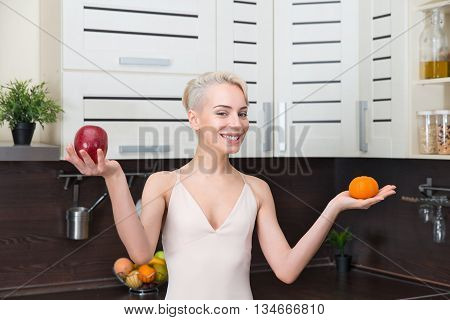 Portrait girl holding apples and orange fruit her hands in modern kitchen. Natural organic raw fresh food concept .