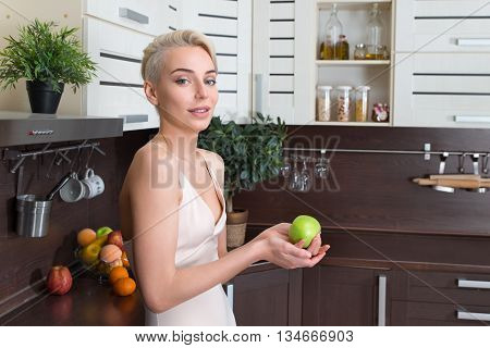 Beautiful blond woman with green apple in kitchen