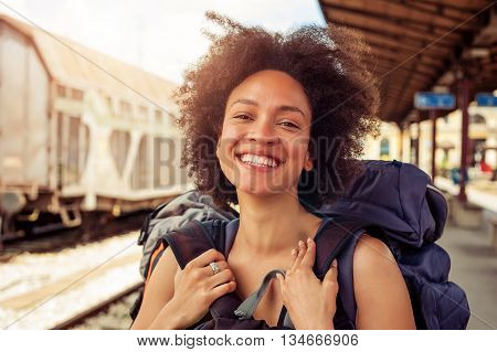Closeup of beautiful tourist traveler standing with huge luggage at the railway station near the tracks