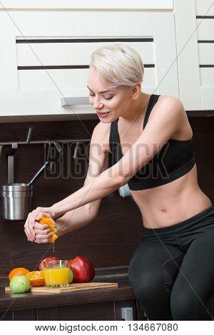 Beautiful blond holding orange juice at home