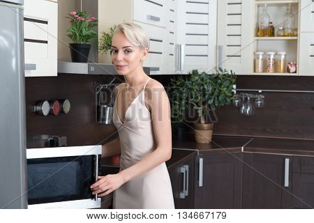 Blond woman cooking with a microwave in modern kitchen