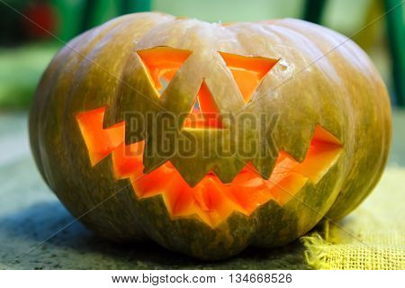 Head of a smiling Pumpkin for Halloween. Trappings of Halloween in a pumpkin head with a candle inside. Main symbol of holiday is Jack-o-lantern.
