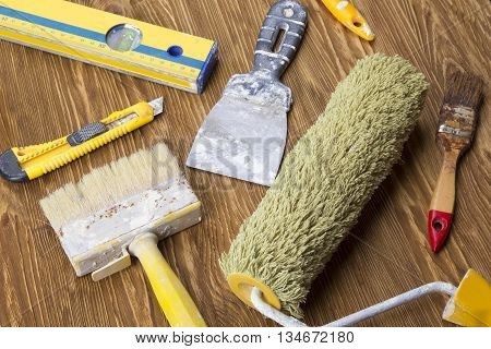 Construction tools: level, trowel, roller, knife and brush on wooden background