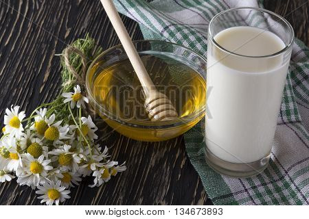 Bowl with honey, glass with milk and chamomile flowers on the wooden table