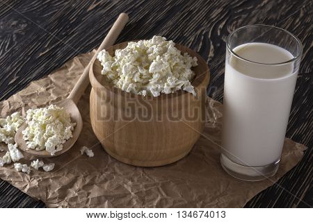 Cottage cheese and glass with milk on wooden background.