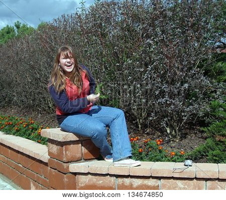 Young girl sitting on the garden jamb