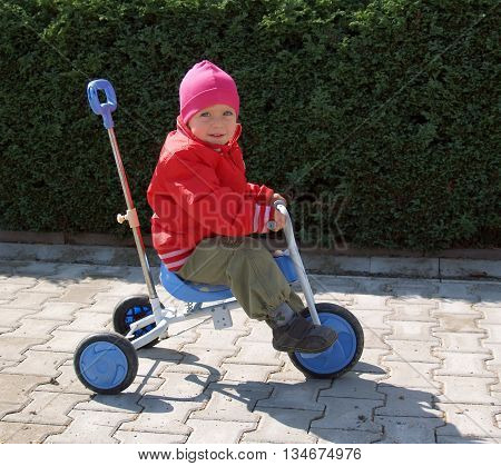 Little preschool girl riding on blue tricycle