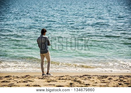 Full Length Shot of a Handsome Athletic Young Man in Trendy Attire seen from the back, on a Beach in a Sunny Summer Day, Looking Away against Blue Sea Background.