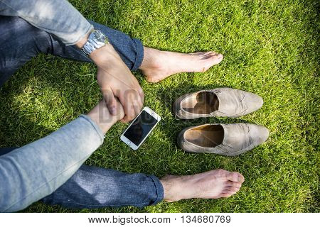 Unrecognizable barefoot man with shoes and cell on grass in sunlight.From above