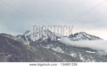 Cold winter clouds moving over snowy Alps with foothills and timber line in foreground