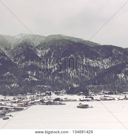 Scenic Overview of Small Resort Village Nestled in Snow Covered Valley Surrounded by Mountain Alps Covered with Thick Evergreen Forest on Overcast Day with Low Lying Clouds, Achenkirch, Austria