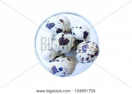 Bowl with quail eggs on a white background top view