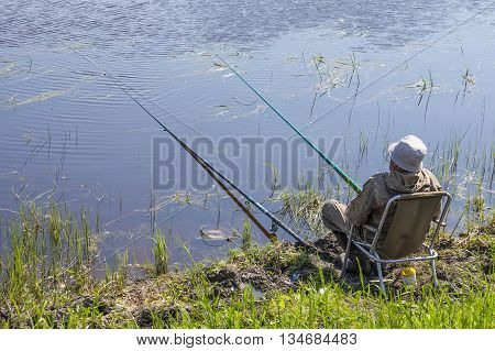 The river Kargat Novosibirsk oblast Siberia Russia - June 12 2016: a fisherman catches a fish on the river on a float
