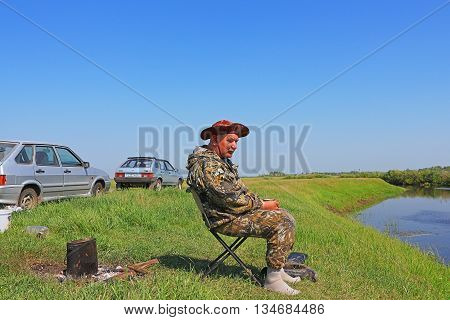 The river Kargat Novosibirsk oblast Siberia Russia - June 12 2016: fisherman drinking tea and admiring the beauty of the river