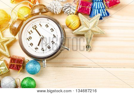Alarm clock and christmas decortions on wood background.
