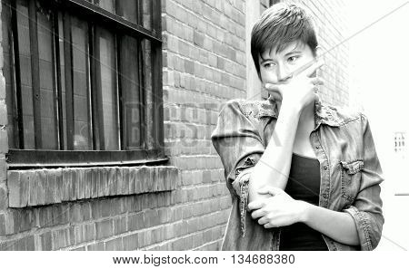 Female beauty fashion model expressions outside against a wall.