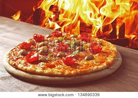 Tasty hot pizza with cherry tomatoes on wooden table on fire flame background