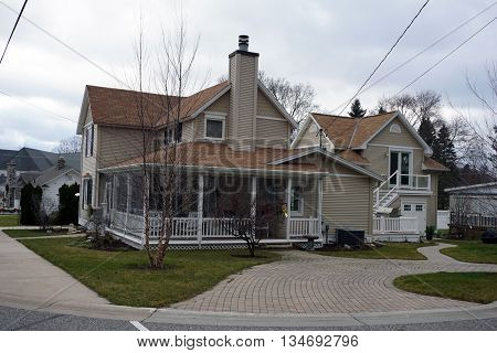 HARBOR SPRINGS, MICHIGAN / UNITED STATES - DECEMBER 24, 2015: A Victorian home with a wraparound porch and a brick driveway on a corner lot in Harbor Springs, Michigan.