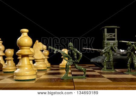 Chess pieces and toy soldiers on a chessboard