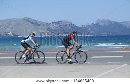 Mallorca Spain - May 4 2016: Cyclist passes a typical beach on the boardwalk at Alcudia Beach.