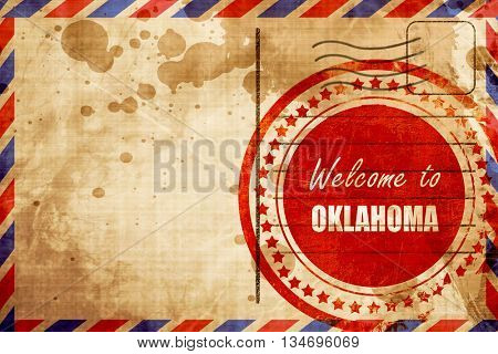 Welcome to oklahoma, red grunge stamp on an airmail background