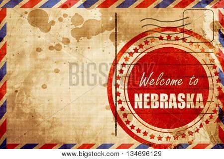 Welcome to nebraska, red grunge stamp on an airmail background
