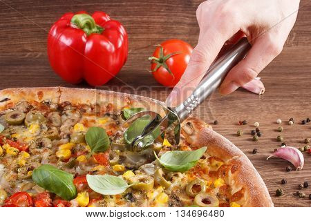Hand Cutting Vegetarian Pizza, Ingredients With Spices On Wooden Background, Fast Food