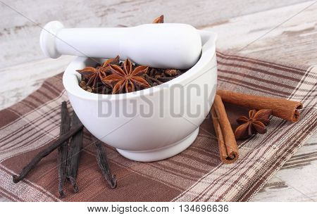 Fragrant Cloves And Anise In Mortar And Spices On Rustic Board
