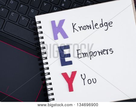 Word spell and handwriting word Knowledge Empower You on notebook with laptop keyboard