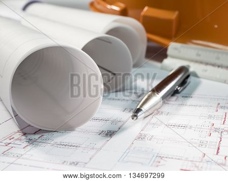 Architect rolls and plans technical project drawing and pen (Selective focus)
