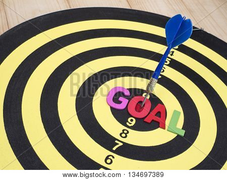 Word spell GOAL on dart board with blue arrow wood background (Business Concept)