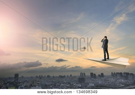 business man on paper plane flying above urban scene spying shot by binocular lens business conception concept