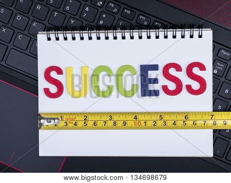 Word spell Success and measuring tape on notebook with laptop keyboard