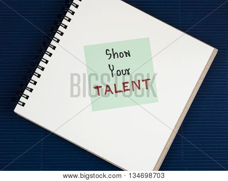 Handwriting Show Your Talent on blank notebook with blue paper background. (Business concept)