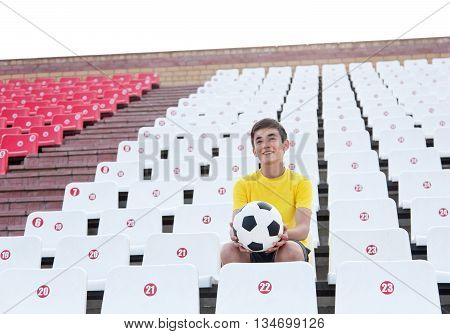 Happy Teenager With Soccer Ball In His Hands Sitting On Tribunes