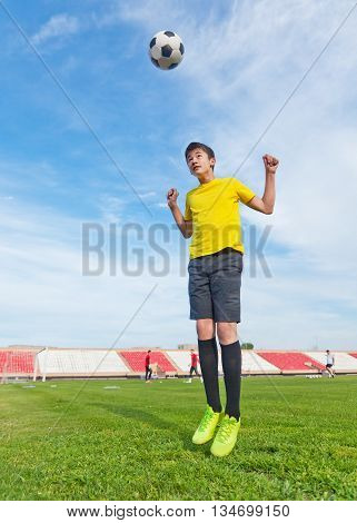 Asian Teenager Boy  In A Football Stadium, Practicing. Jump And Hits The Ball Head