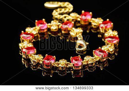 Ruby gold bracelet isolated on black background