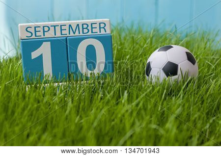 September 10th. Image of september 10 wooden color calendar on green grass lawn background. Autumn day. Empty space for text. World First Aid Day.