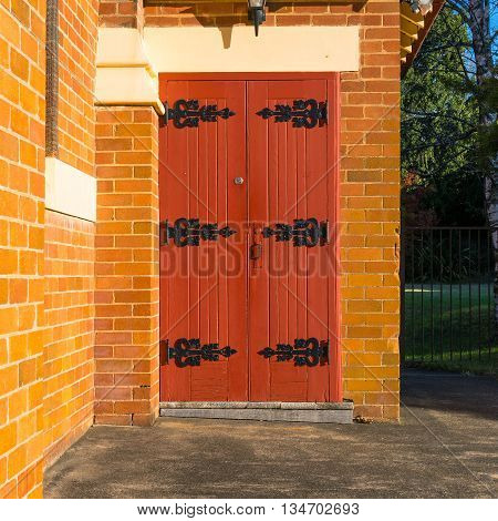 Wooden dark red church door with black hinges