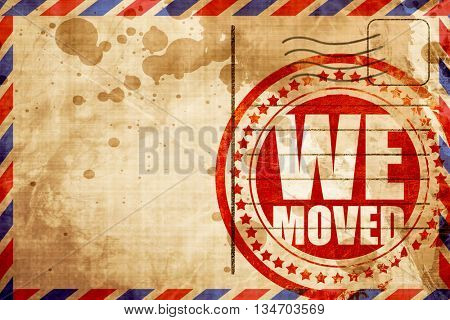 we moved, red grunge stamp on an airmail background