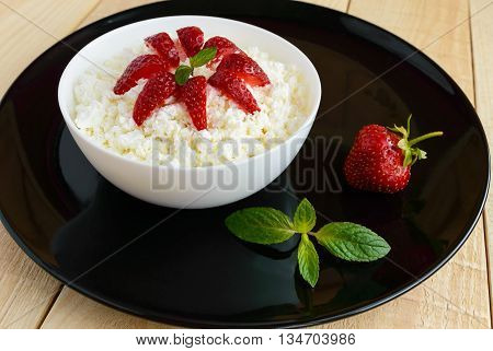 Homemade cottage cheese with fresh strawberries mint leaves decoration in white bowl on black dish. Useful eco breakfast. Healthy eating.