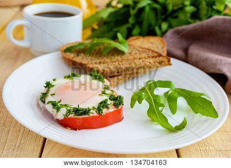 Scrambled eggs baked in a ring bell pepper toast arugula leaves and a cup of coffee. Light breakfast.