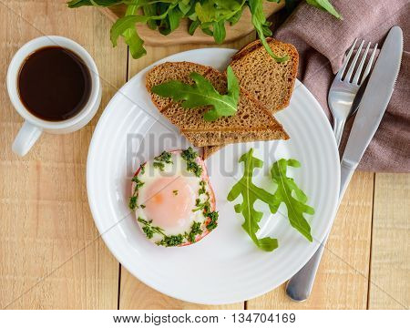 Scrambled eggs baked in a ring bell pepper toast arugula leaves and a cup of coffee. Light breakfast. The top view