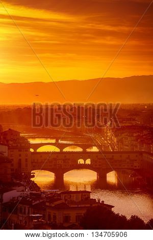 Gold sunset at bridge ponte vecchio in florence old town on arno river italy