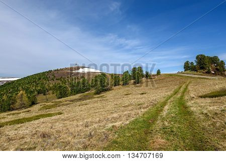Scenic view with telecommunications tower on top of a mountain road and trees against a blue sky on a sunny summer day