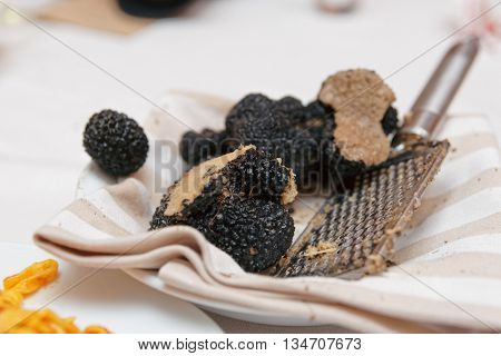 Grated black truffle on plate, close-up