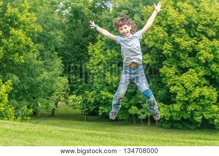 Adorable young child boy in the park. On warm summer day during school holidays. Kid boy jumping and smiling.