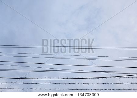 background of cable and barbed wire in cloudy sky
